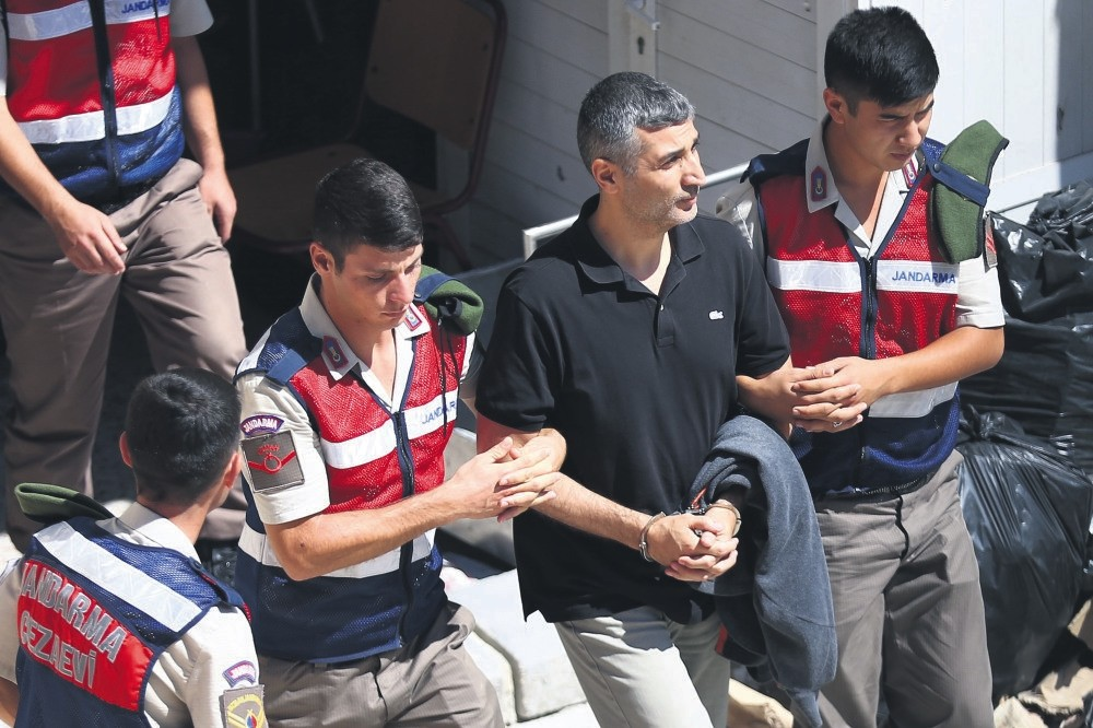 Gendarmerie officers escort Gu00f6khan u015eahin Su00f6nmezateu015f, a former general who plotted the mission to assassinate President Erdou011fan in yesterday's hearing.