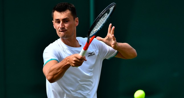 Australia's Bernard Tomic returns against France's Jo-Wilfried Tsonga during their men's singles first round match at the 2019 Wimbledon Championships in southwest London, on July 2, 2019. AFP Photo