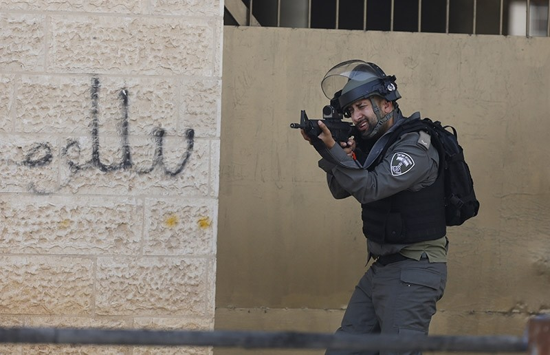 An Israeli border policeman aims his weapon at Palestinian during clashes in the West Bank city of Bethlehem, Friday, July 21, 2017. (AP Photo)