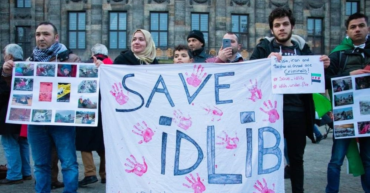 Demonstrators hold signs in the Dutch capital Amsterdam while protesting attacks on civilians in Idlib, Syria, Dec. 28, 2019 ( Abdullah A??ran - Anadolu Ajans? )
