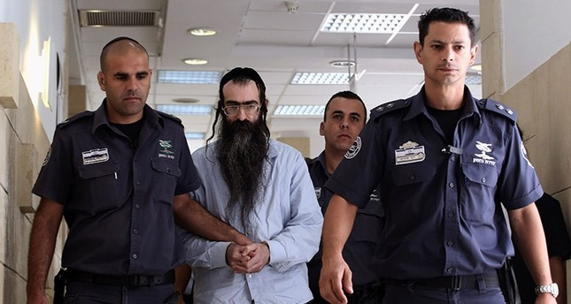 Ultra-Orthodox Jew Yishai Shlissel (C), who was convicted of killing a 16-year-old Israeli girl during the Jerusalem Gay Pride parade last year, is escorted by policemen into the courtroom, on June 26, 2016 (AFP Photo)