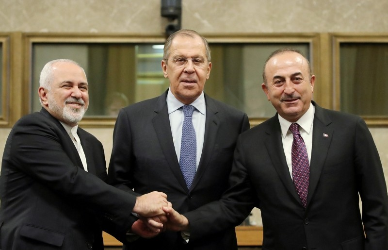 Russian Foreign Minister Lavrov, Turkish Foreign Minister u00c7avuu015fou011flu and Iranian Foreign Minister Zarif shake hands as they attend a news conference after talks on forming a constitutional committee in Syria, at the U.N. in Geneva. (REUTERS Photo)