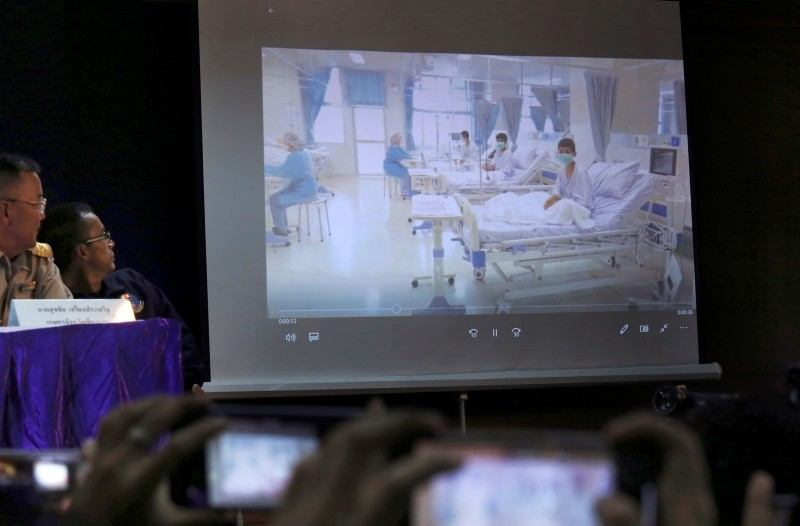 Members the media try to photograph a projected image of the rescued boys in their hospital room during a police press conference in Chiang Rai province, northern Thailand, Wednesday, July 11, 2018. (AP Photo)