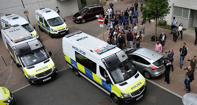 Police vans leave carrying a number of women who were detained after a block of flats was raided in Barking, east London, Britain, June 4, 2017. (Reuters Photo)