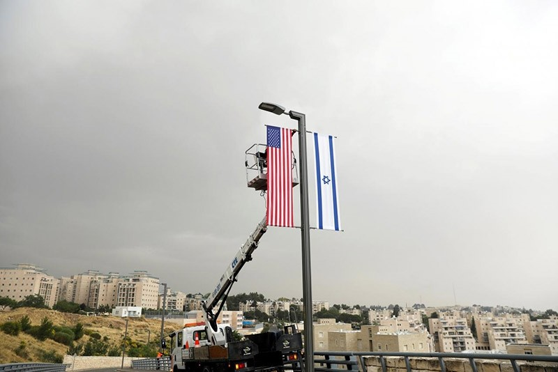 A worker on a crane hangs a U.S. flag next to an Israeli flag, next to the entrance to the U.S. consulate in Jerusalem, May 7, 2018. (Reuters Photo)