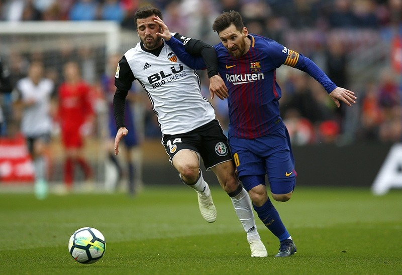 FC Barcelona's Lionel Messi, right, vies for the ball with Valencia's Jose Luis Gaya during the Spanish La Liga soccer match between FC Barcelona and Valencia at the Camp Nou stadium in Barcelona, Spain, Saturday, April 14, 2018. (AP Photo)