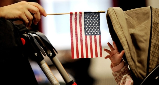 A baby reaches for an American flag held by her mother during naturalization ceremony at a federal building in New York, January 14, 2011. (EPA Photo)