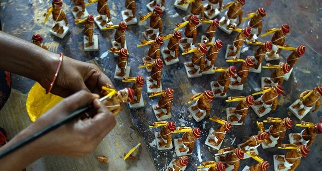 In this file photo taken on December 18, 2008, an Indian artisan applies vegetable paint to toys at a workshop in Kondapalli village in Vijayawada district of Andhra Pradesh state. (AFP Photo)