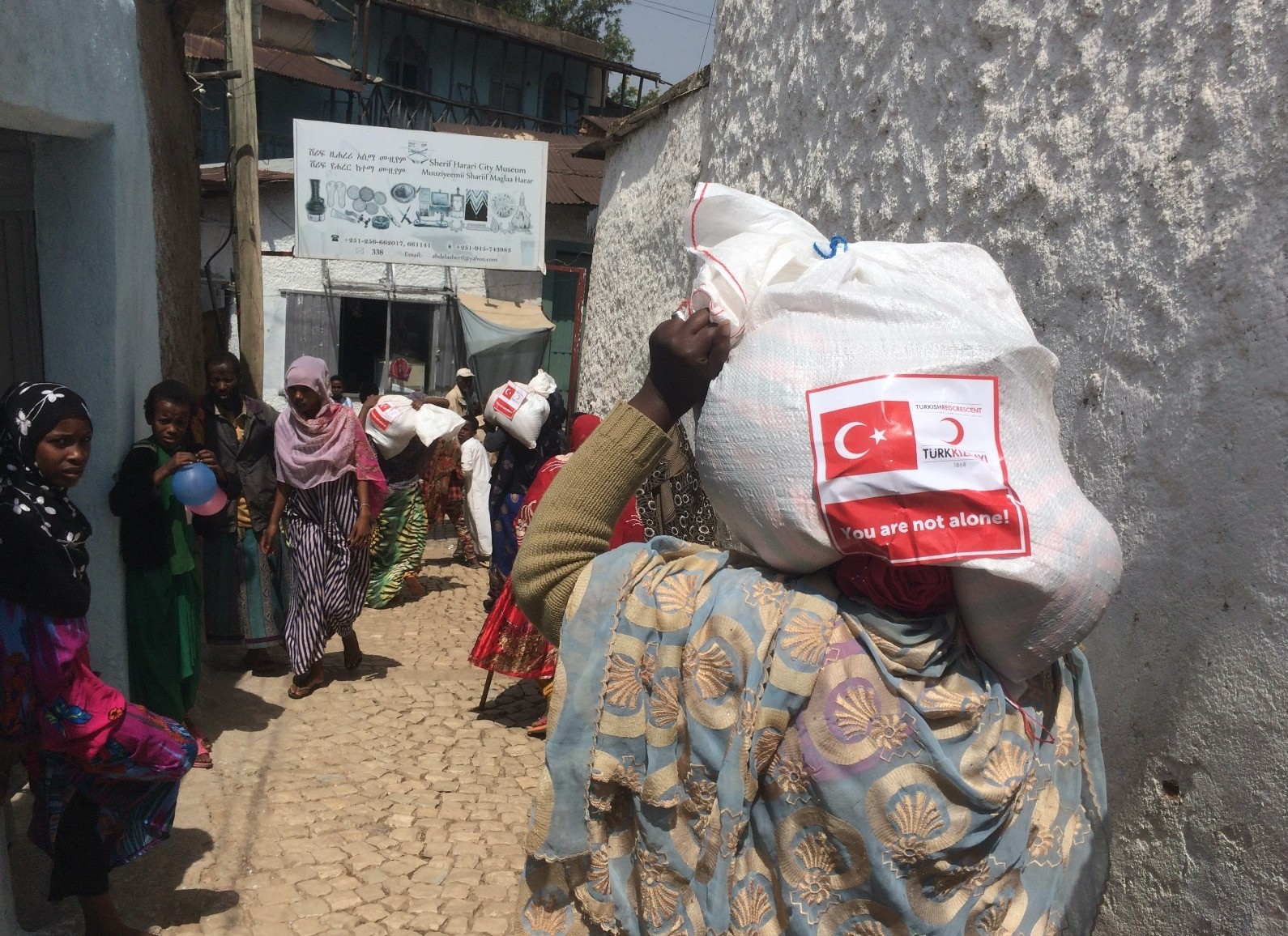 A woman in Ethiopiau2019s Harar carries a food package donated by the Turkish Red Crescent.