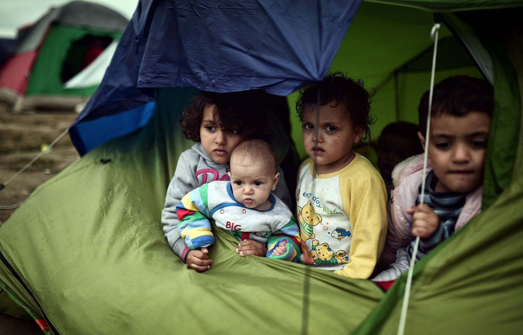 Refugee children sit in a tent in the makeshift camp at the Greek-Macedonian border near Idomeni, March 7, 2016.