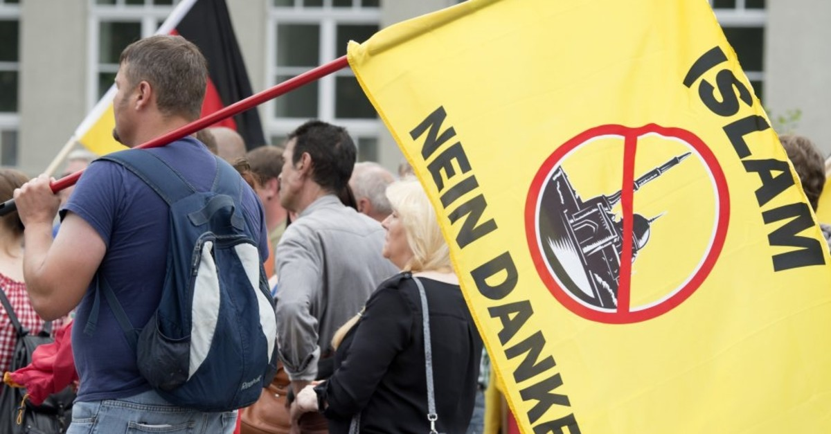 A supporter of a right-wing organization holds a flag reading ,Islam, No Thanks, during a rally, Erfurt, June 4, 2016.