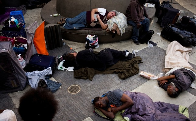 A group of homeless people sleep in the courtyard of the Midnight Mission in Los Angeles. The mission's courtyard is open to all homeless people looking for a safe place to spend the night. (AP Photo)