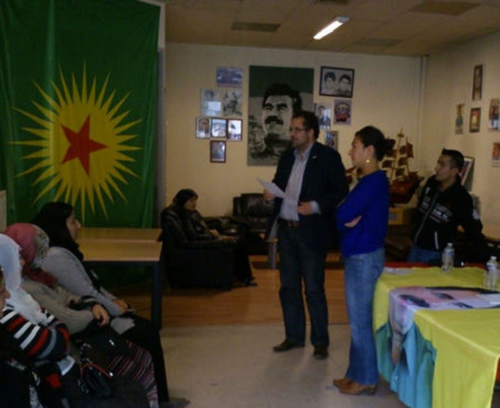 A picture of the imprisoned PKK leader Abdullah u00d6calan hangs in the background as Demir (R) attends an event organized by PKK symphatizers.