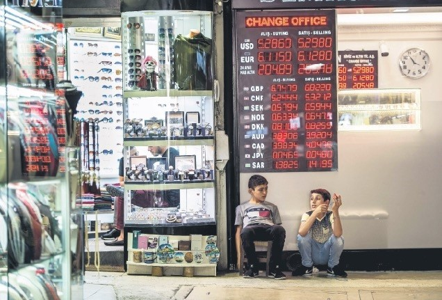 Two boys sit in front of an exchange office in Istanbul at a time when the Turkish lira is rapidly losing value against the U.S. dollar, Aug. 8.