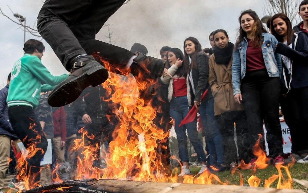 People jumping over a bonfire at a Nevruz celebration in an Istanbul park.