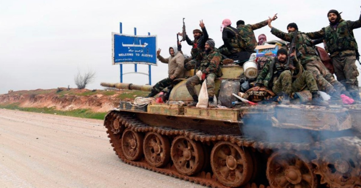 In this photo released Wednesday, Feb. 12, 2020, by the Syrian regime's news agency SANA, Assad forces on a tank hold up their rifles and flash victory signs, as they patrol the highway that links the capital Damascus with the northern city of Aleppo