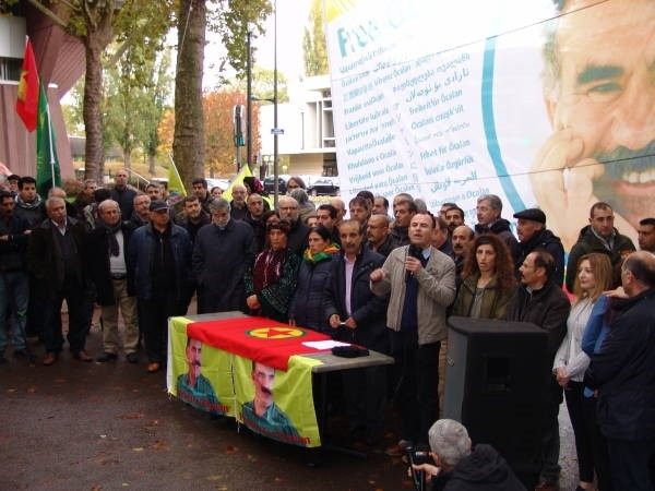 PKK supporters gather behind the poster of the jailed leader of their group