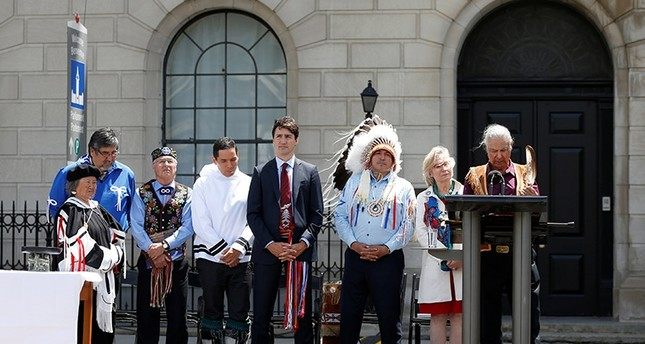 Canada's Prime Minister Justin Trudeau (C) listens to a prayer during an event announcing the creation of a new space for Indigenous Peoples at 100 Wellington Street (Reuters Photo)
