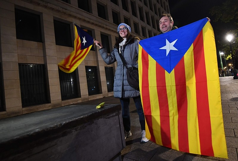 A man and a woman hold the Catalan flag as they stand outside the public prosecutor's office in Brussels, Belgium, Nov. 5, 2017. (AFP Photo)