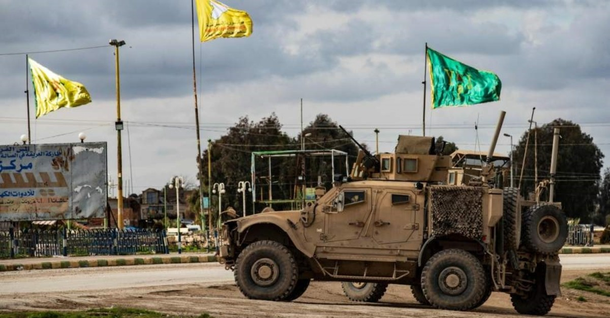 A patrol of US military vehicles is seen near the flying yellow flags of the terrorist YPG-dominated SDF and green flags of its constituent YPJ in the town of Tal Tamr in the northeastern Syrian Hasakah province along the border with Turkey on Feb. 8, 2020. (AFP Photo)