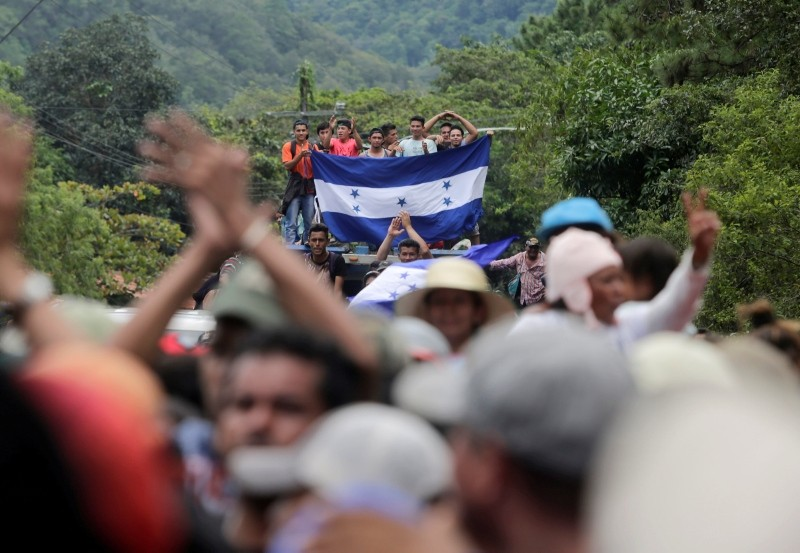 Honduran migrants, part of a caravan trying to reach the US, gesture while arriving to the border between Honduras and Guatemala, in Agua Caliente, Guatemala, Oct. 15, 2018. (Reuters Photo)