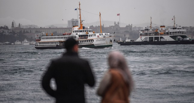 A Turkish couple awaits a ferryboat near the Bosporus strait on a rainy and windswept morning in the Karaköy district of Istanbul, Jan. 11.