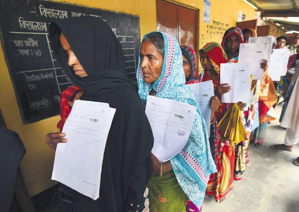 Residents hold their documents as they stand in a queue to check their names on the final list of National Register of Citizens (NRC) at a NRC Sewa Kendra (NSK) in Burgoan village in Morigoan district on Monday. (AFP Photo)