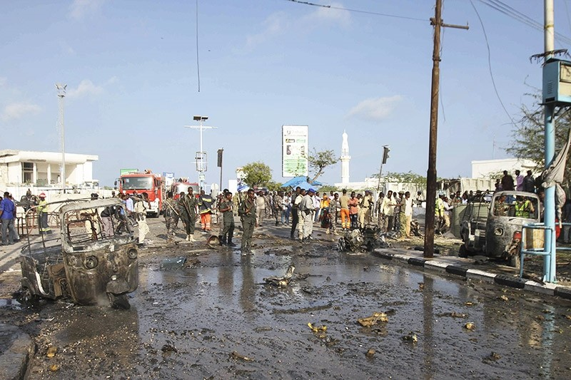 Somali security officers gather around the remains of destroyed vehicles at the scene of a car bomb explosion in the capital Mogadishu, Somalia. (EPA Photo)