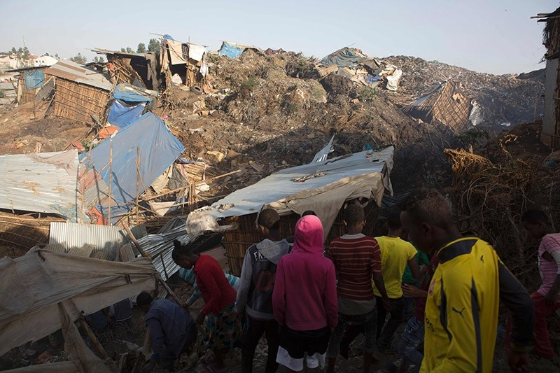 People look at the damage done to dwellings built near the main landfill of Addis Ababa on the outskirts of the city on March 12, 2017, after a landslide left at least 50 people dead. (AFP Photo)