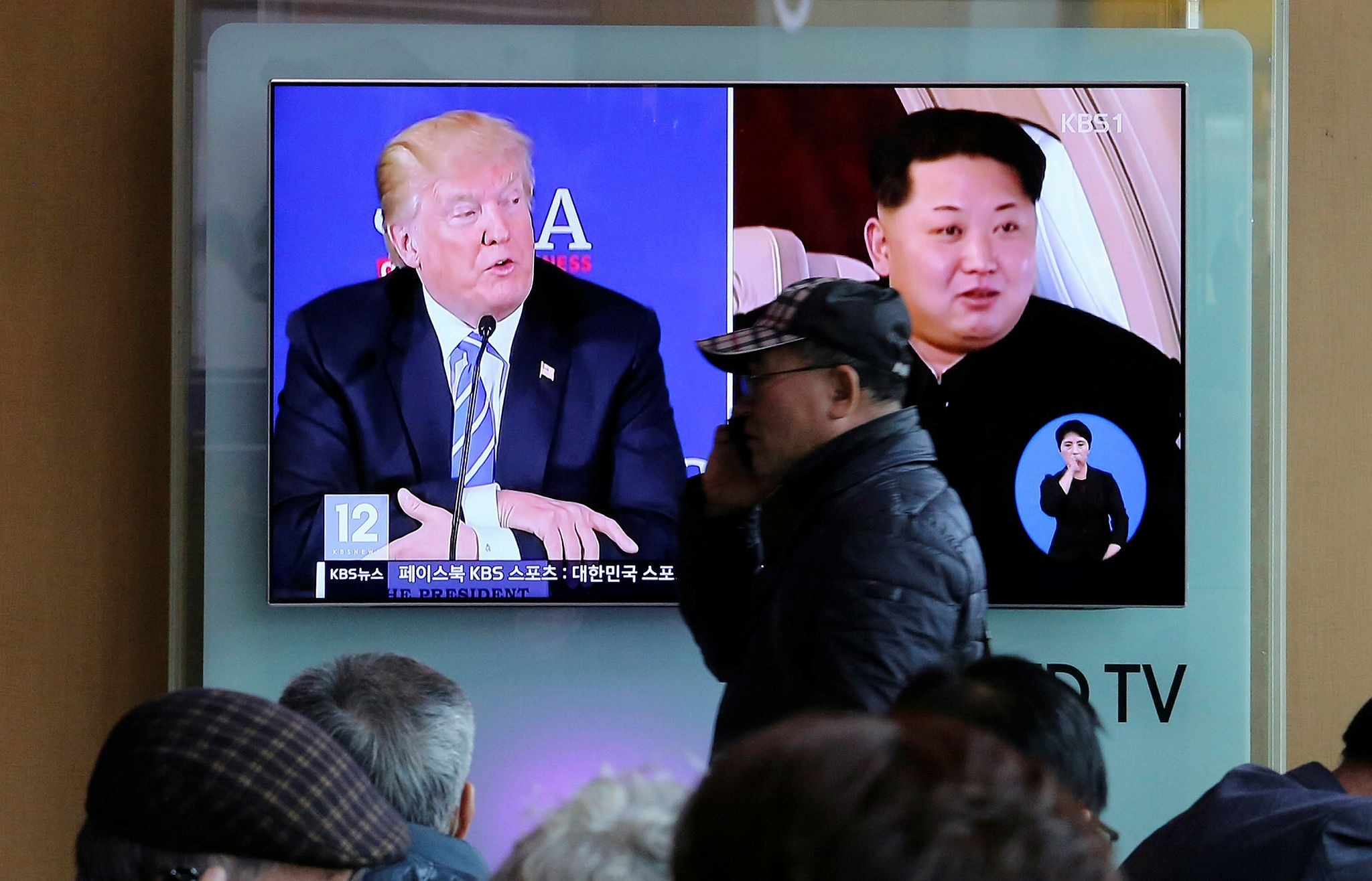 A man passes by a TV screen showing file footage of U.S. President  Donald Trump (L) and North Korean leader Kim Jong-Un during a news program at the Seoul Railway Station, April 9.