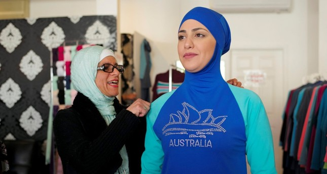 Aheda Zanetti (L), designer of the burkini swimsuit, adjusts one of the swimsuits on a model at her fashion store in Sydney.