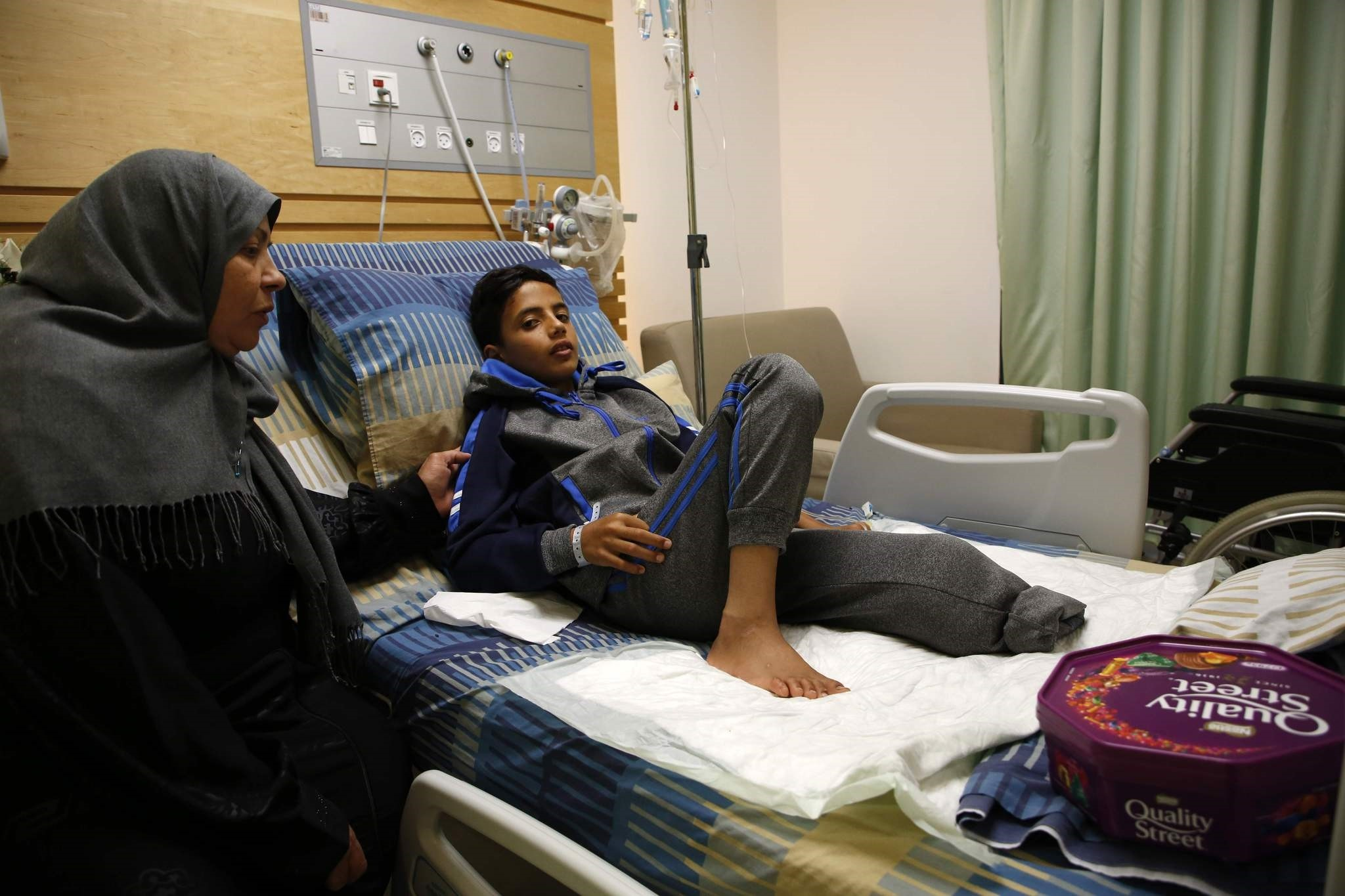 Abdel Rahman Nawfal, 12, sits next to his grandmother in a hospital in the West Bank city of Ramallah on April 23, 2018. (AFP Photo)