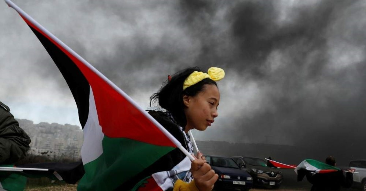 A girl holds a Palestinian flag during a protest against U.S. President Donald Trump's Middle East peace plan, in the village of Bilin in the Israeli-occupied West Bank, Feb. 7, 2020. (REUTERS Photo)