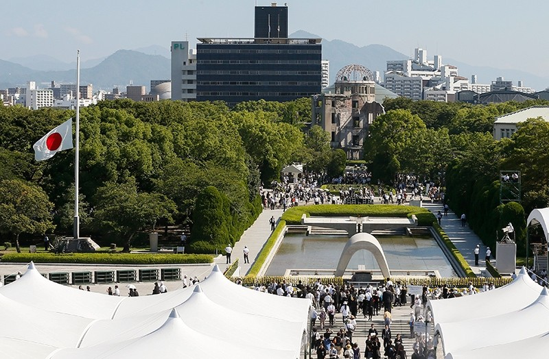 Citizens walk toward a cenotaph to offer prayers for victims of the August 6, 1945 atomic bombing as the Japanese flag flies at half mast during a memorial ceremony at the Hiroshima Peace Memorial Park in Hiroshima, Japan, August 6, 2017. (EPA Photo)