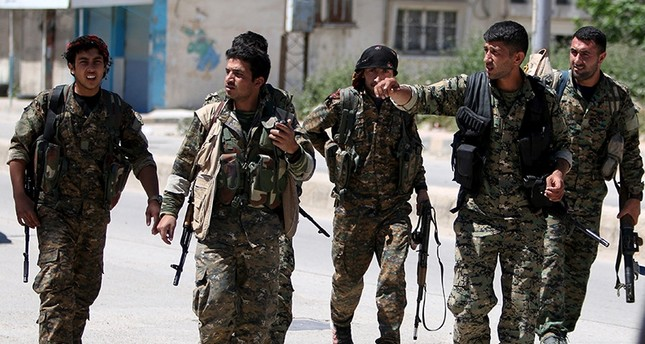 People's Protection Units (YPG) terrorists walk along a street in the southeast of Qamishli city, Syria, April 22, 2016. (Reuters Photo)