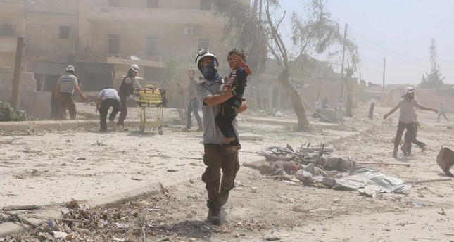 A Syrian rescue worker carries a child in Aleppo after regime aircrafts dropped barrel bombs.