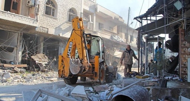 Syrian men use an excavator to clear rubble following a reported Syrian airstrike in the town of Saraqib, in the northwestern Idlib province on Dec. 21, 2019. AFP