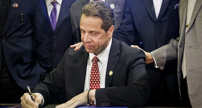 FILE - In this April 10, 2017, file photo, New York Gov. Andrew Cuomo signs new legislation for free state college tuition and juvenile justice reform, during a signing ceremony in New York (AP Photo)