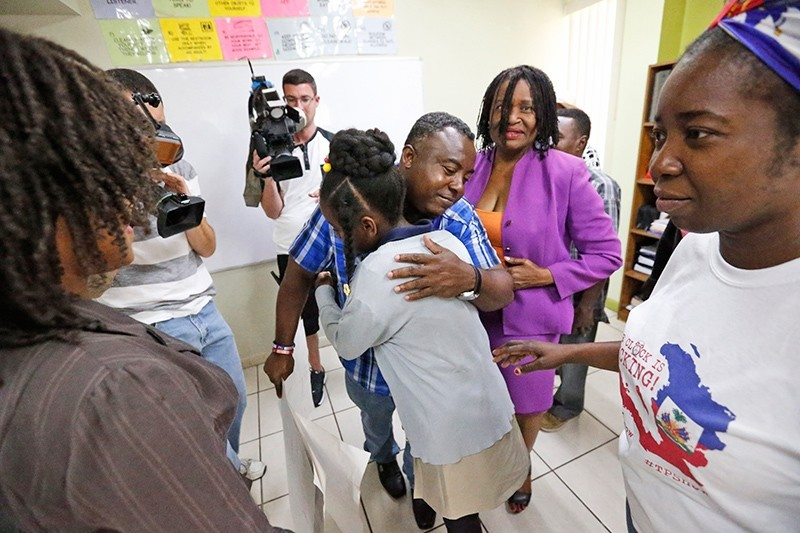 In this May 22, 2017, file photo, Pierrot Mervilier, center rear, hugs a girl that did not wish to be identified, living in the U.S. with Temporary Protected Status (TPS) after she and her family spoke to members of the media in Miami. (AP Photo)