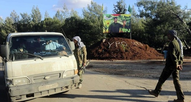 PYD terrorists stop a car, with PKK leader Abdullah Öcalan's picture in the background (Reuters Photo)