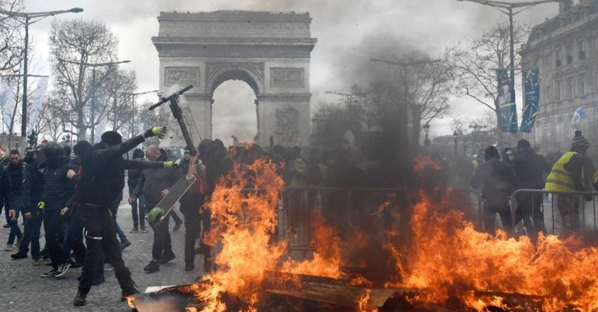 Yellow vest protesters face police forces as clashes erupt at the Champs Elysees, Paris, March 16, 2019. (EPA Photo)