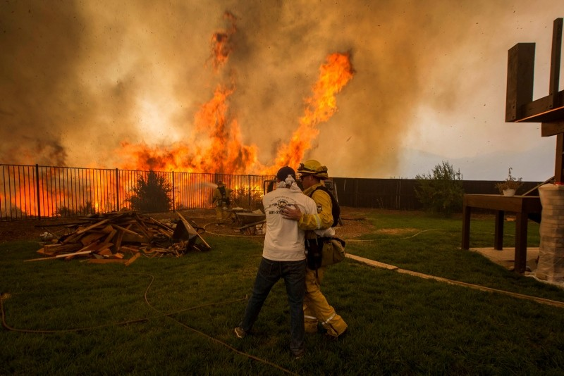 A firefighter consoles a man who is worried that his sister's house (R) will burn during the Holy Fire in Lake Elsinore, California, USA, 09 August 2018. (EPA Photo)