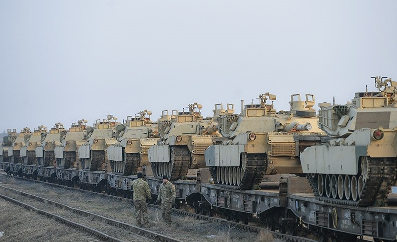 Servicemen of the ,Fighting Eagles, 1st Battalion, 8th Infantry Regiment, walk by tanks that arrived via train to the US base in Mihail Kogalniceanu, eastern Romania, Tuesday, Feb. 14, 2017. (AP Photo)