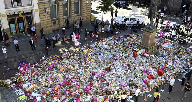 People stand around flower tributes for the victims of Monday's bombing at St Ann's Square in central Manchester, Britain, Friday, May 26 2017. (AP Photo)