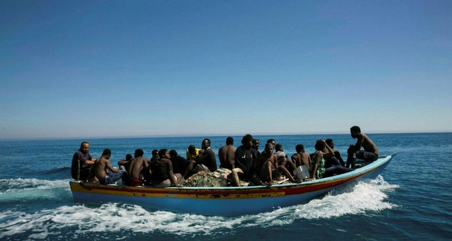 Migrants travel in a boat after they were rescued by the Libyan coast guard in the Mediterranean off the Libyan coast in Guarabouli, July 8.