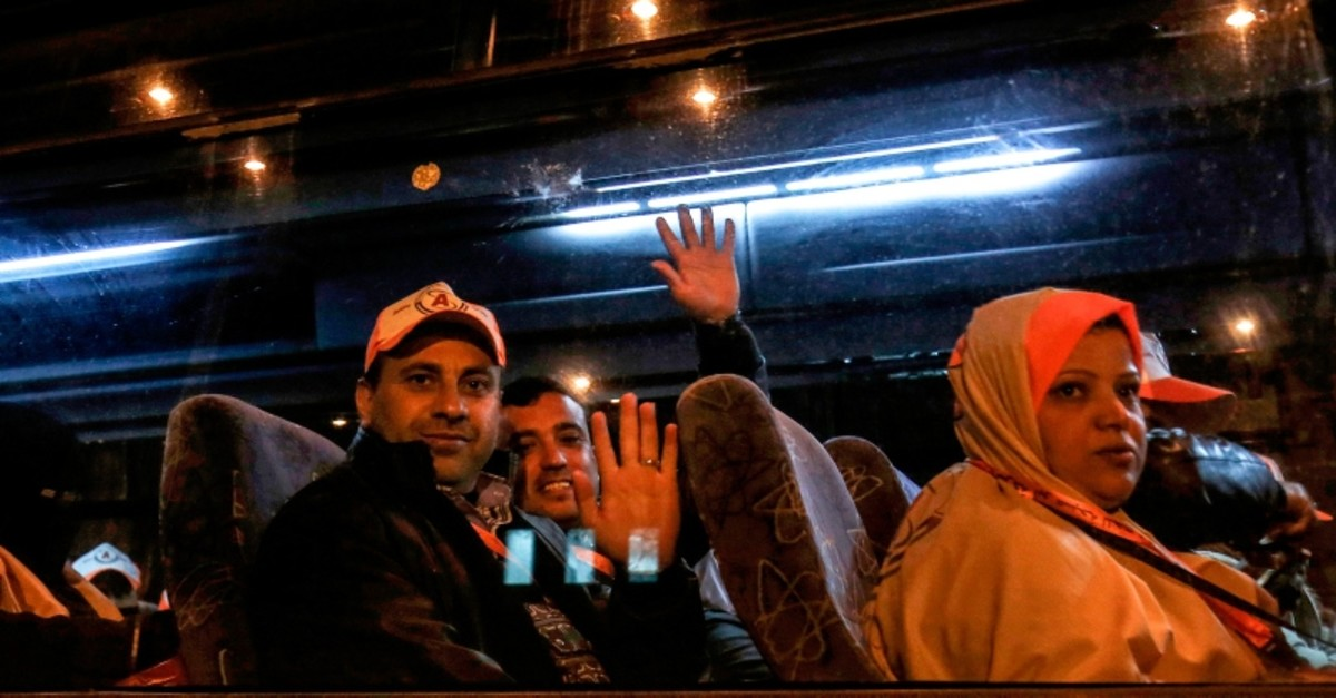Palestinians Muslim pilgrims wave to their relatives as they sit in a bus at the Rafah border crossing between the Gaza Strip and Egypt before crossing to depart for umrah pilgrimage for the first time since 2014, Sunday, March 3, 2019. (AFP Photo)
