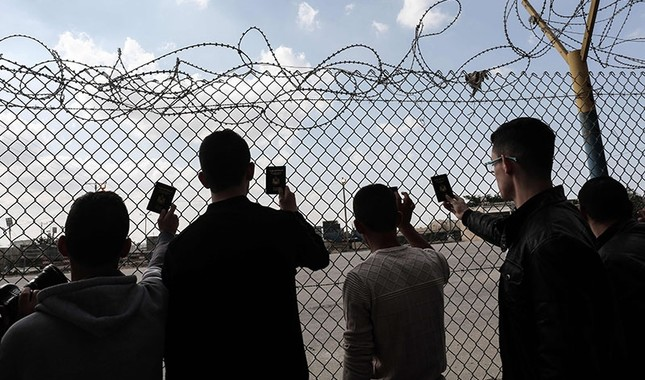 Palestinian young men use their smart-phones as they wait to cross at the Rafah border crossing with Egypt before being allowed to pass out of the southern Gaza Strip, Nov. 20, 2017. (AFP Photo)