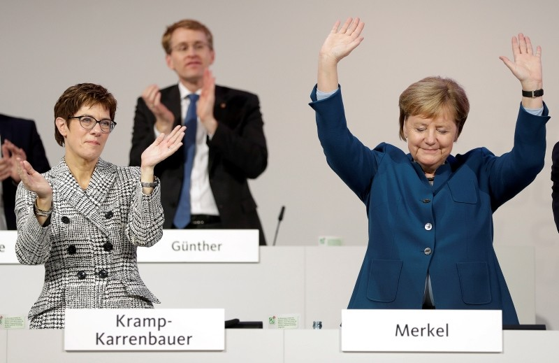 German Chancellor Angela Merkel, right, is flanked by Annegret Kramp-Karrenbauer, the newly elected chairwoman of the Christian Democratic Union (CDU), after her farewell speech during a party convention in Hamburg, Germany, Dec. 7, 2018. (AP Photo)