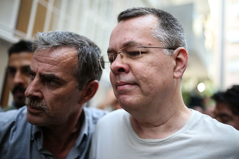 U.S. terror-linked pastor Andrew Craig Brunson (R), escorted by Turkish plain clothes police officers arrives at his house on July 25, 2018 in Izmir. (AFP Photo)