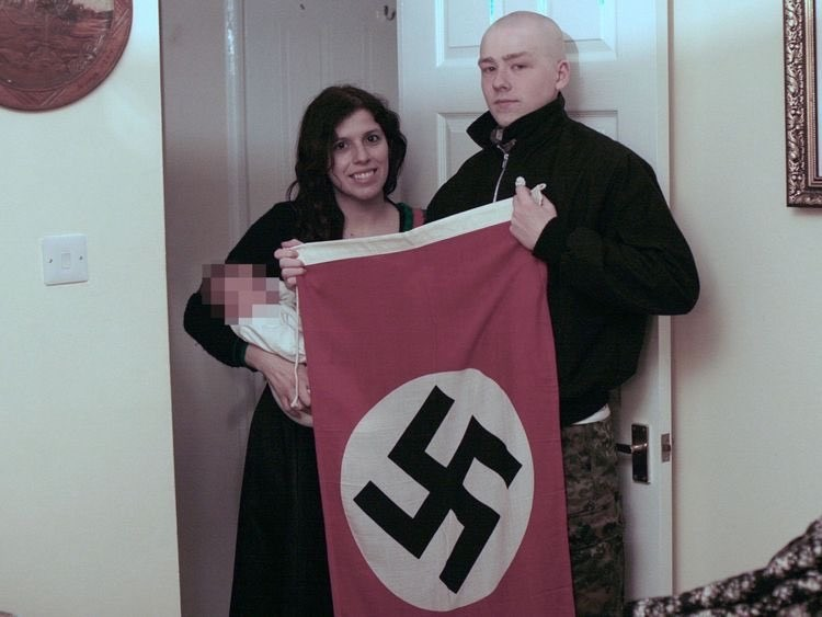 Claudia Patatas and Adam Thomas pose for a with their baby while holding a flag of Nazi Germany. (Photo: West Midlands Police/PA)
